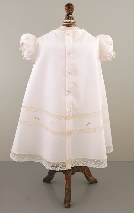 Light pink Christening gown with five-button back, lace inserts, puff sleeves, and a t-shaped yoke with embroidery.