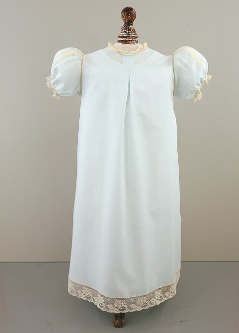 Light blue Christening gown with five pearlescent buttons down the front, lace inserts in the yoke, puff sleeves and a lace collar.