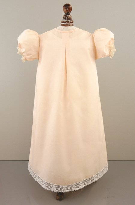 Delicate peach-colored Christening gown with five buttons down the front, soft floral embroidery and lace inserts.