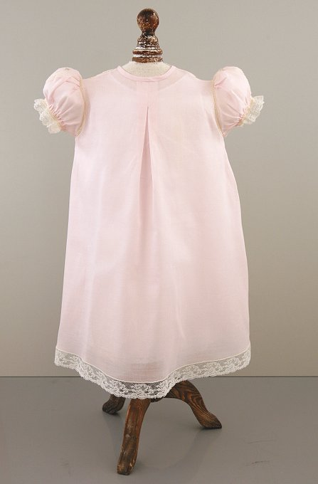 Lacey, four-button Christening gown with puff sleeves, intricate floral embroidery, and lace inserts in the yoke.