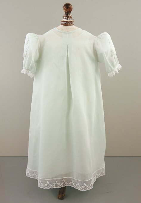Lacey, five-button Christening gown with puff sleeves, intricate embroidery, and lace insets.